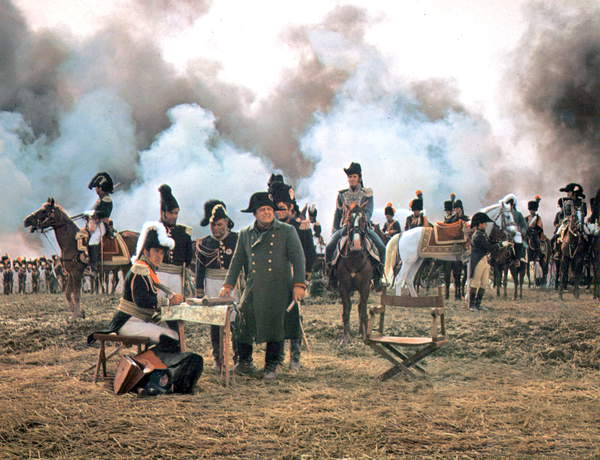 Image showing Napoleon I at the Battle of Waterloo, he stands by a table with an open map, horses and soldiers appear in the background. The clouds are grey and atmospheric. The actor that plays Napoleon I is Rod Steiger. © Dino de Laurentiis Cinematografica/Mosfilm / Collection CSFF / Bridgeman Images