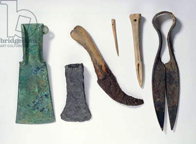 Selection of tools: L-R: early Iron Age bronze axe with bent-over wings; later iron axe; knife with a bone handle; bone needle; bone awl; iron shears