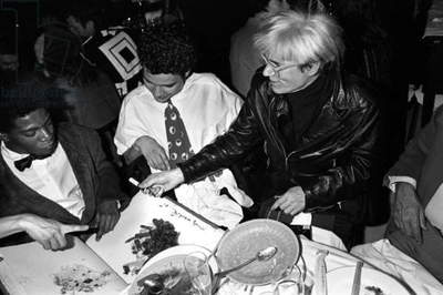 Andy Warhol passing a pen to Jean-Michel Basquiat at Mr Chow, New York, 1985 (b/w photo)