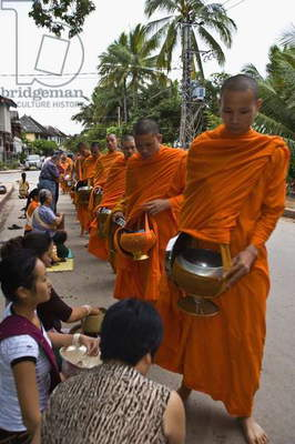 Buddhist Monk Getting Offerings from Crowd (photo)