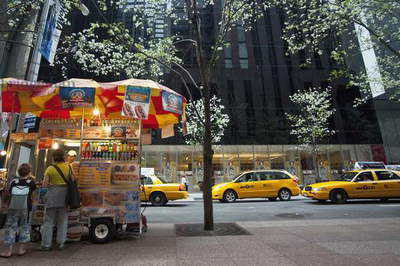 Man Selling Hot Dogs  and Taxis Passing in Front of The Museum of Modern Art Also Known As Moma, Manhattan, New York, USA (photo)