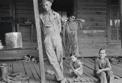 Floyd Burroughs, Alabama sharecropper, on his porch with neighbors children, 1936. By Walker Evans