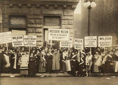 Crowd of women's suffrage supporters demonstrating with signs reading, 'Wilson Against Women,' in Chicago on October 20, 1916. Wilson withheld his support for Votes of Women until 1918
