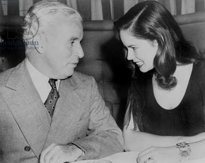 Charlie Chaplin (1889-1977) sitting with his young wife Oona at Hollywood nightclub in 1944. The couple married the previous year, when Oona was 18 and Charlie was 54