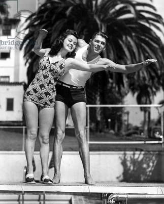 Ronald Reagan uses his lifeguard background to demonstrate swimming technique to Susan Hayward in a Warner Brothers publicity photo, 1938