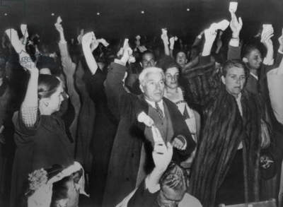 Charlie Chaplin with wife Oona at Hollywood Bowl campaign rally for Henry Wallace in 1948. The audience are holding dollar bills in their hands and Chaplin pledged $1000 to the campaign