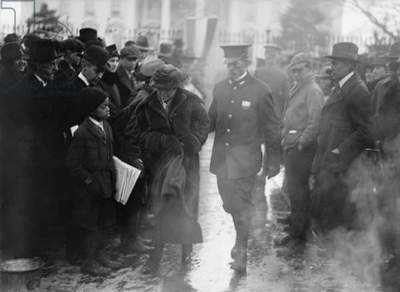 Policeman leads an arrested National Woman's Party protestor away from a woman's suffrage bonfire demonstration at the White House in 1918