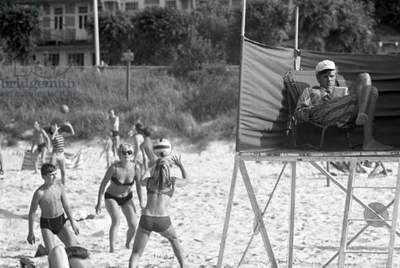 Ustka, Poland, 1970. People on the beach playing volleyball close to a lifeguard on his post.