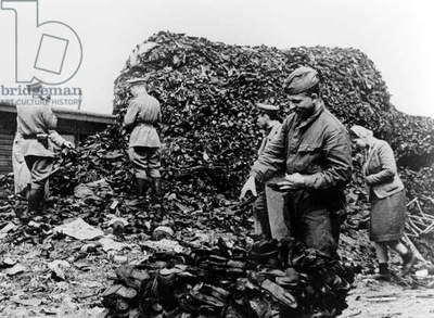 Russian soldiers inspecting a pile of clothing items at Auschwitz concentration camp, 28th January 1945 (b/w photo)