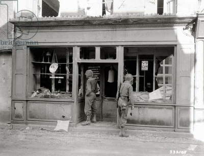 Two GIs looking into a store that has been damaged, Couterne, Normandy, France, August 1944 (b/w photo)