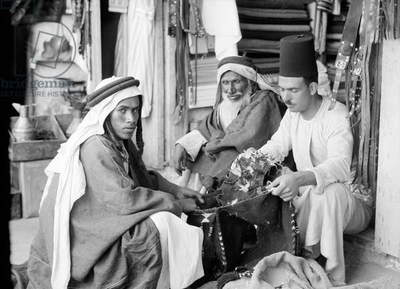 MIDDLE EAST: BEDOUINS, 1932 A group of Bedouin men seated at a shop in the Middle East, 1932.