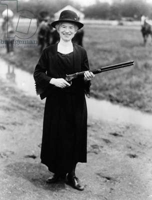 ANNIE OAKLEY (1860-1926) American markswoman. Photographed with the rifle Buffalo Bill gave her, 1922.