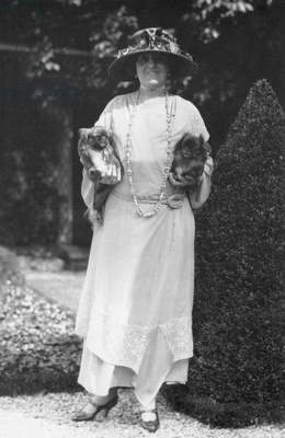 EDITH WHARTON (1862-1937) American writer. Photographed at her home in France with with her two pet Pekingese dogs, 1920s.