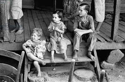 Impoverished migrant children sitting on a porch in Hale County, Alabama, 1936 (b/w photo)