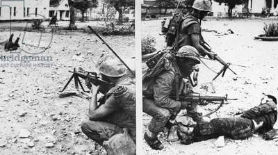 VIETNAM WAR: TET OFFENSIVE. In the city of Hue a U.S. Marine takes aim at a wounded enemy soldier, wanting to surrender, and then, with a comrade, moves to secure the prisoner, February 1968.
