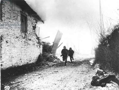 WWII: BELGIUM Two American soldiers of the 3rd Armored Division advance under enemy fire at Mont-le Ban, Belgium, January 1945.