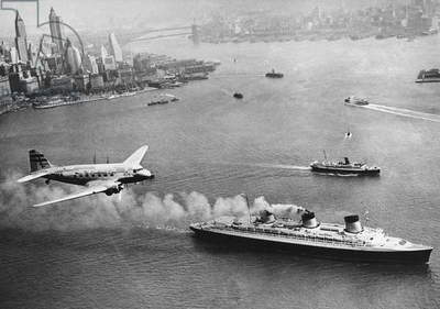 PLANE AND OCEAN LINER, 1938 Aerial view of New York Harbor, 1938, showing a TWA airliner flying above the French ocean liner S.S. 'Normandie.'