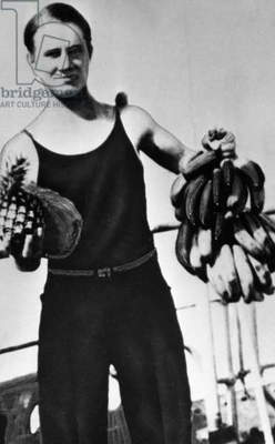 HENRIK KURT CARLSEN ( c.1914-1989). Danish-born American sea captain and captain of the SS Flying Enterprise. Carlsen became famous when he stayed on the sinking freighter alone for 13 days in January 1952. Carlsen photographed holding bunches of tropical fruit, 1930s or 1940s.