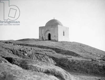 MIDDLE EAST: BUILDING, c.1932 A Bedouin man outside a small building in the Middle East. Photograph, c.1932.