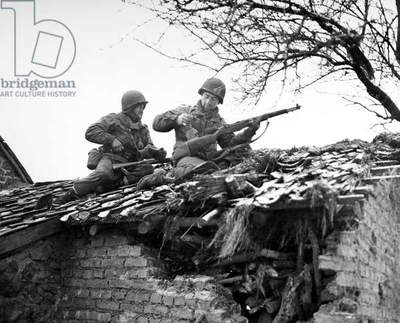 WORLD WAR II: BELGIUM American rifleman on a rooftop in Beffe, Belgium, snipe German snipers. Photographed 7 January 1945.
