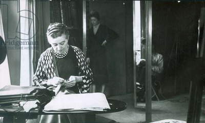 JEANNE LANVIN (1867-1946) French fashion designer. Scrutinizing fabrics in her office at the House of Lanvin in Paris, 1937.