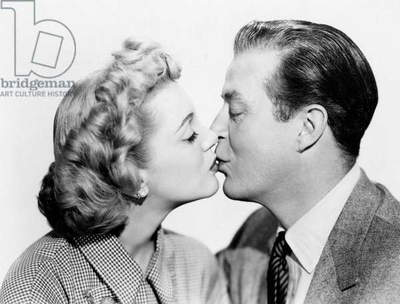 Jan Sterling and Ray Milland engage in a tender kiss, United States