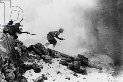 A British officer armed with a revolver leading his men forward with fixed bayonets, one of seven official photographs relating to the 2nd Battle of El Alamein, 1942 (b/w photo)