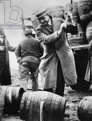 A US Federal agent broaching a beer barrel from an illegal cargo during the American Prohibition era (1920-33) (b/w photo)