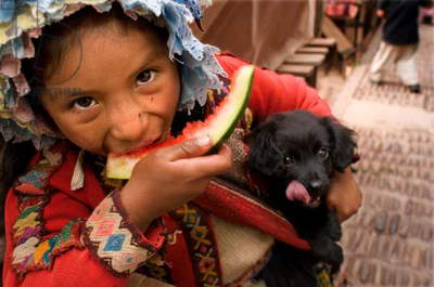 A girl dressed in a traditional costume eating a piece of watermelon on Sunday market day, Pisac, Peru (photo)