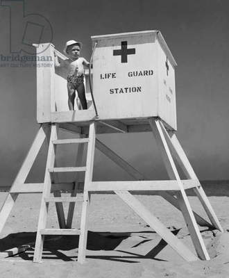 Boy standing on a lifeguard station on the beach