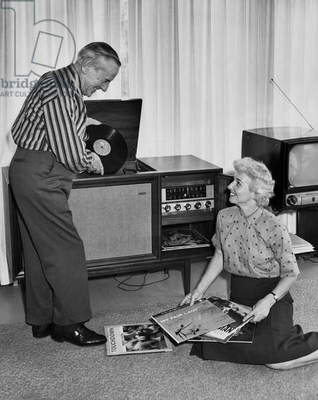 Senior couple listening to music from vinyl records