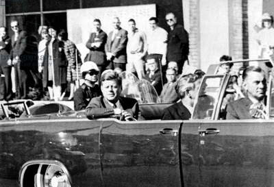 American president John F. Kennedy rides with Texas Governor John Connally (c) and Jackie Kennedy (hidden behind Connally) in an open car a few minutes before his assassination in Dallas, Texas novembre 22, 1963