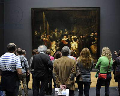 Visitors looking at The Night Watch by Rembrandt (1606-1669). Rijksmuseum. Amsterdam.   Netherlands