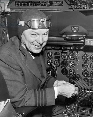 San Francisco, California: 1958 A pilot wearing old time aviation head gear and goggles in the cockpit of a modern airplane.  (b/w photo)