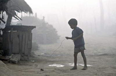 A child playing with a wooden top, in a village, in the Chitwan region, in Nepal.  (photo)