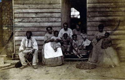 Family of slaves at the Gaines' house. Published 1861 or 1862. African American slave family or families posed in front of wooden house, Washington, D.C. or Hampton, Virginia.