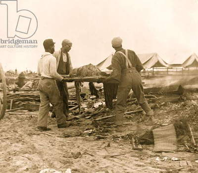 Galveston disaster, carrying dead body to fire to be burned 1900 (photo)