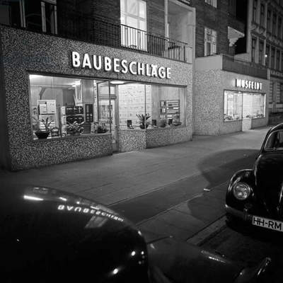 Front side of the outlet of architectural hardware company Musfeldt at Hamburg by night, Germany 1960s