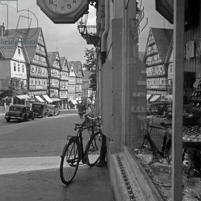 Houses and a street reflecting in the window of a clock and household hardware shop at Bad Wildungen, Germany 1930s (b/w photo)