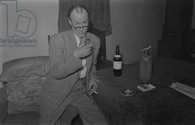Comedy pose with a drink. Chuck O'Neil, a comedian, pictured at the home of Dr E.A. Stroud, College Street, Nuneaton. November 1954