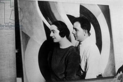 Photograph of Sonia and Robert Delaunay in front of the painting 'Helice' (1923) by Robert Delaunay at the Exhibition 'Sonia Et Robert Delaunay' at the Bibliotheque Nationale, Paris, 1977 (b/w photo)