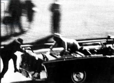 Jackie Kennedy scrambles for help for her mortally wounded husband, President Kennedy, after he was hit by an assasin's bullet during the cotorcade. A secret service man is rushing (left) during the President's assassination in Dallas, Texas novembre 22, 1963