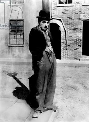 A dog 's life by and with Charlie Chaplin (the tramp) , standing in a street, hands in pockets. Los Angeles (Chaplin Studios), 1918.