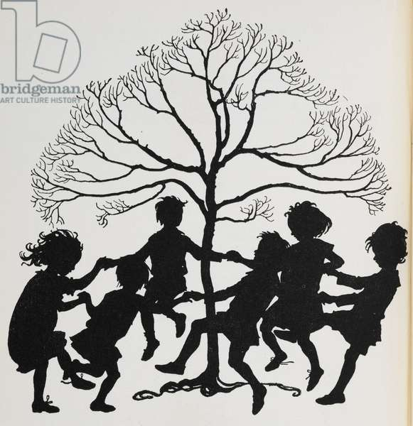 Silhouette of children dancing around a tree.
