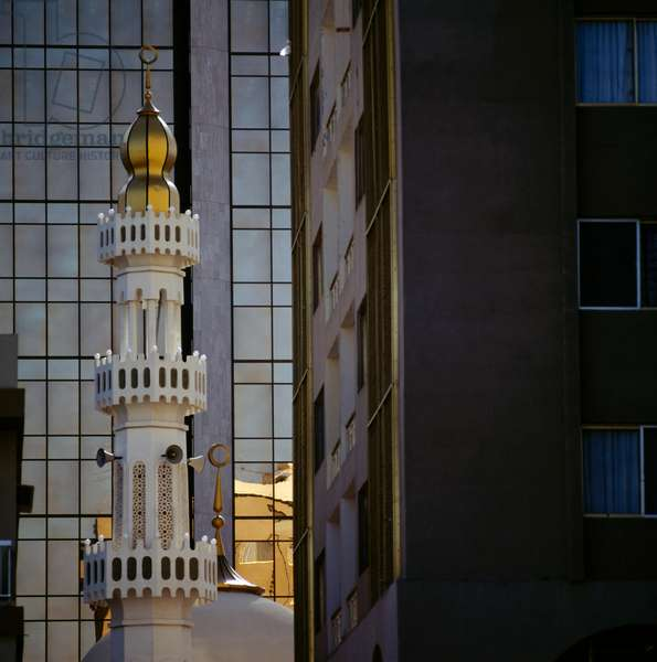 Minaret in traditional style with skyscraper in background, Abu Dhabi, United Arab Emirates