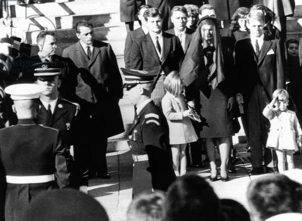 Three year old John F. Kennedy Jr. salutes his father's flag draped coffin after funeral mass at St. Matthew's Cathedral. Family members from center, L_R: Sen. Edward Kennedy; Caroline Kennedy; Peter Lawford; Jacqueline Kennedy; Robert Kennedy; and John Jr. Nov. 25, 1963