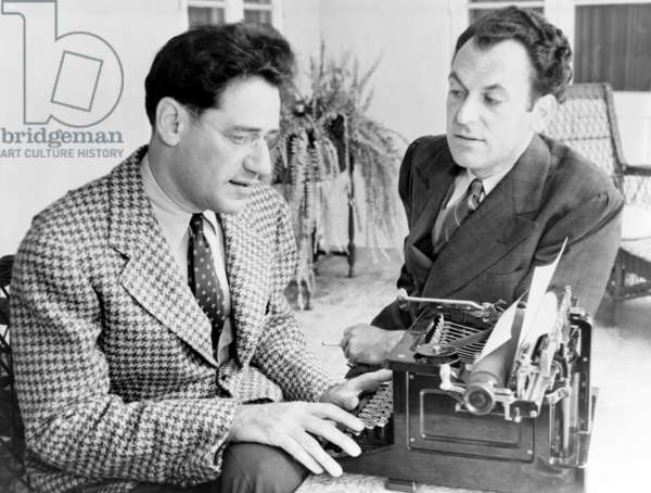 George S. Kaufman (1889-1961) typing while Moss Hart (1904-1961) talks, in 1937, the year their play, YOU CAN'T TAKE IT WITH YOU, won the Pulitzer Prize