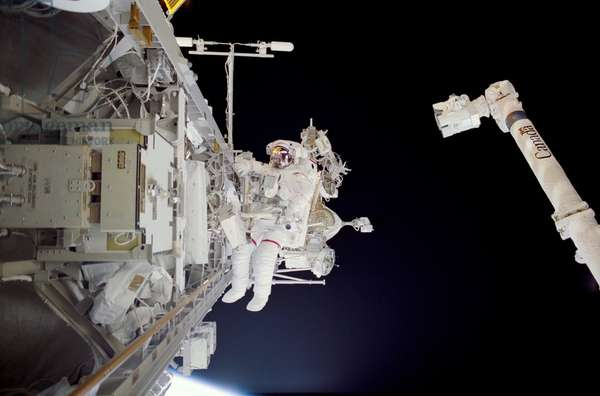 Construction work on International Space Station. Astronaut Michael Lopez-Alegria in a space walk near the Canadarm while assembling the International Space Station's backbone. Nov. 30, 2002