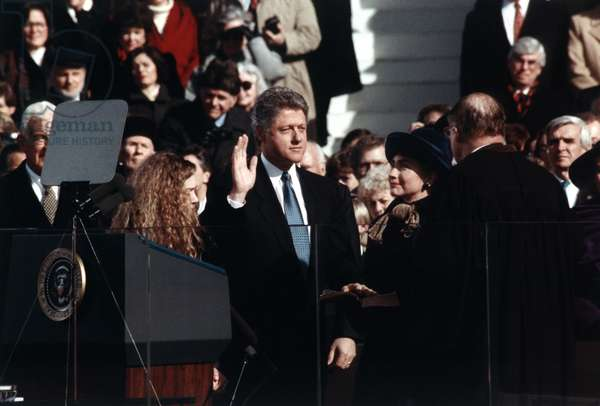 President Bill Clinton takes the oath of office administered by Chief Justice William Rehnquist. Wife Hillary Rodham Clinton and daughter Chelsea Clinton look on. Jan. 20, 1993