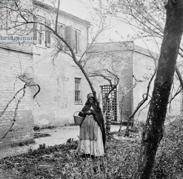 Exterior of the slave pen of Price, Birch & Co., dealers in slaves, of Alexandria, Virginia with an African American women standing in foreground. Slave pens, were prisons, to hold slaves awaiting sale. c. 1863